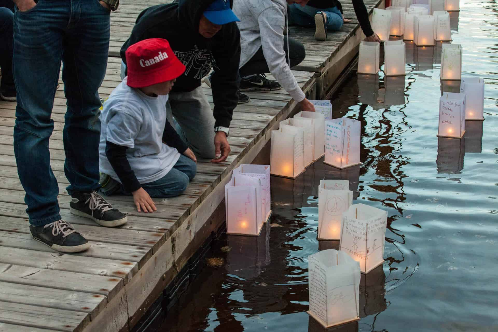 Photo of families launching paper lanterns on water.